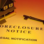 A key and model house lying on a legal notification for a foreclosure.